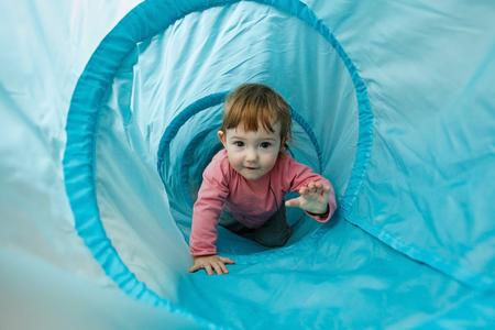 小さな幼児トンネル チューブで遊んでそれを介してクロールと楽しい時を過します。家族の楽しさ、早期教育と経験の概念を学習します。 写真素材