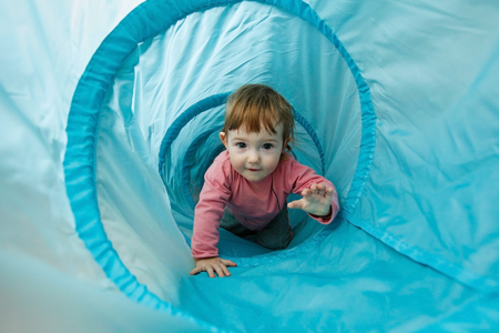 Small toddler playing in a tunnel tube, crawling through it and having fun. Family fun, early education and learning through experience concept.