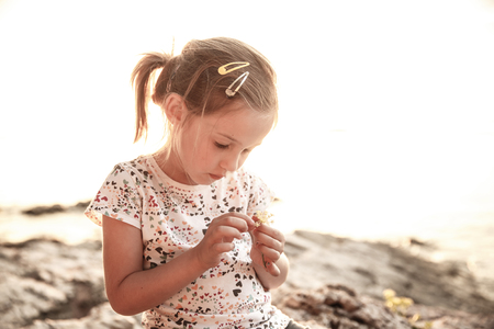 sunlit: Little girl sitting on a sunlit beach at sunset, playing with a flower, having a peaceful vacation time. Childhood, family vacation, child creativity concept.