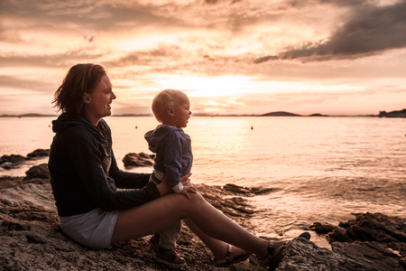 mama e hijo: Madre e hijo que se sientan en una playa rocosa, hablar, jugar y divertirse durante la puesta de sol y disfrutando de su tiempo de vinculación juntos. Los valores familiares, la tranquilidad y la serenidad concepto.