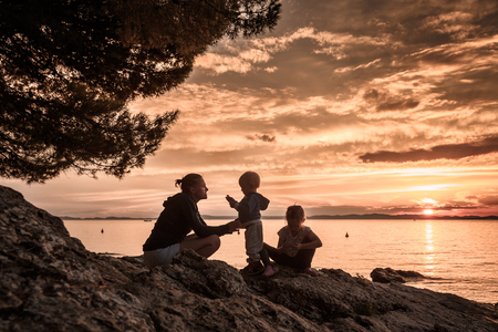 values: Mother with children talking, playing on a rocky beach, watching the sunset and enjoying their bonding time together. Family values, tranquility and serenity concept.