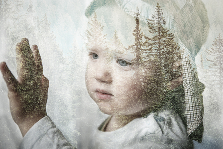 Little boy daydreaming, looking out the window at nature, thinking about it. Double exposure of child portrait and forest landscape. Hope, dreaming, back to nature, future, sustainability concept.