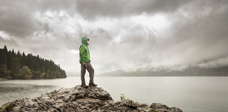 man outdoors: Man standing on a rock beside a dramatic mountain lake after a hike in the rainy, gloomy day. Active lifestyle, outdoor activities, moods and emotions concept.