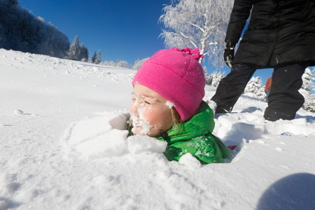 covered in snow: Child with face covered in fresh snow in a beautiful winter landscape, playing and having fun with her family. Active lifestyle, family bonding and fun, happy childhood concept. Stock Photo