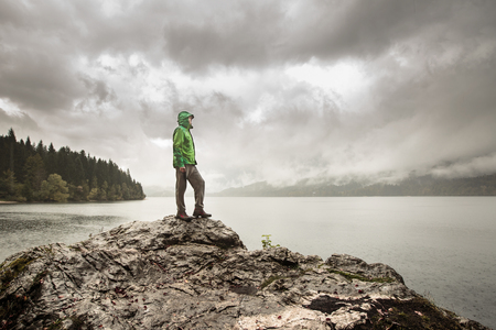 winter forest: Man standing on a rock beside a dramatic mountain lake after a hike in the rainy, gloomy day. Active lifestyle, outdoor activities, moods and emotions concept.