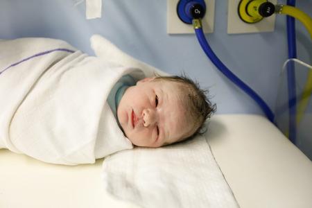 Moe maar gezonde pasgeboren, gewikkeld in een deken, het waarnemen, liggend op een tafel onder het licht, net nadat hij werd geboren, worden beoordeeld door een verloskundige in de verloskamer in het ziekenhuis. Nieuw leven, geboorte ervaring concept.