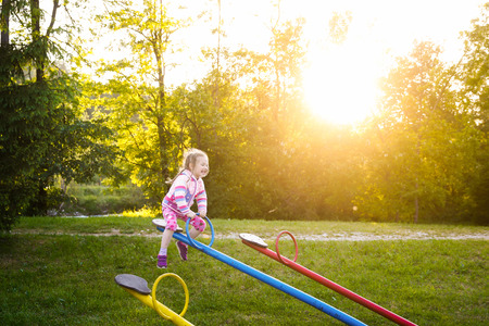 seesaw: Happy little girl playing, going up ad down on a seesaw on a grassy playground in unspoiled nature among trees, sun going down, sunset. Healthy and active childhood concept. Stock Photo