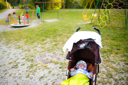 parental control: Baby resting in a stroller, his sibling,friends and mother playing in the background on a playground. Healthy and active childhood, second child concept.