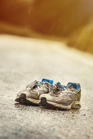 wornout: Worn-out mens running shoes standing on a desolate country road in a rainy day. Sports, active lifestyle, running, marathon, individual sports concept.