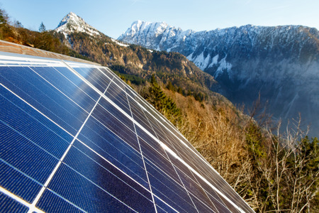 Closeup of photovoltaic solar panels in mountainous natural area, gathering sunlight. Sustainable resources, environmental conservation, alternative power source and generation, green energy concept.
