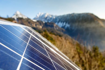 green power: Closeup of photovoltaic solar panels in mountainous natural area, gathering sunlight. Sustainable resources, environmental conservation, alternative power source and generation, green energy concept.