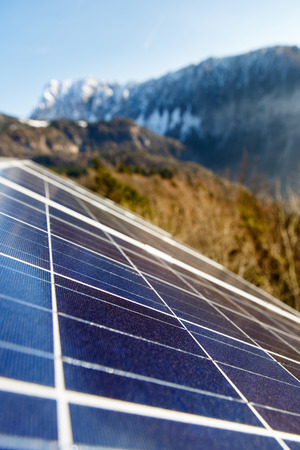 sustainable resources: Closeup of photovoltaic solar panels in mountainous natural area, gathering sunlight. Sustainable resources, environmental conservation, alternative power source and generation, green energy concept.