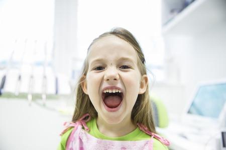 dientes sanos: niña relajada que muestra sus dientes de leche sanos en el consultorio dental, sonriendo y esperando para un chequeo. La prevención temprana, paedodontics y ningún concepto el miedo.