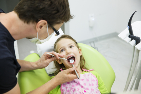 Child patient sitting on dental chair in paediatric dentists office on her regular checkup for caries and gum disease. Early prevention, oral hygiene and milk teeth care concept. Archivio Fotografico