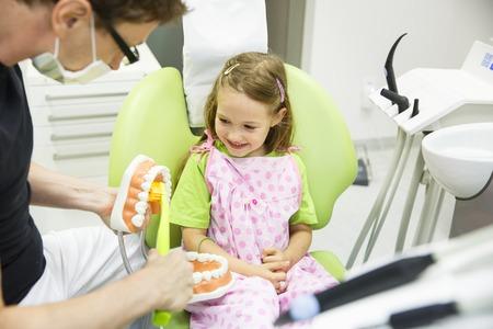 niño modelo: dentista pediátrico educar a una niña sonriente sobre adecuado cepillado de los dientes, lo que demuestra en un modelo. La prevención temprana, la sensibilización, demostración del concepto de higiene oral.