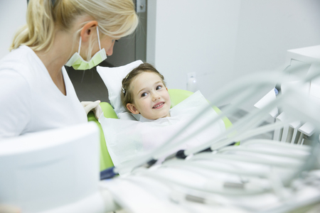 unease: Little patient conversing with her dentist at dental office before her regular checkup for caries and gum disease. Early prevention, oral hygiene and milk teeth care concept. Stock Photo