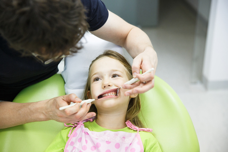 unease: Little girl in paediatric dentists office on her regular checkup for tooth decay, caries and gum disease.