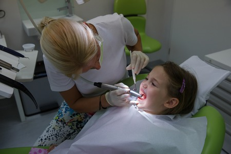 dental fear: Child patient in paediatric dentists office on her regular checkup for tooth decay, caries and gum disease.