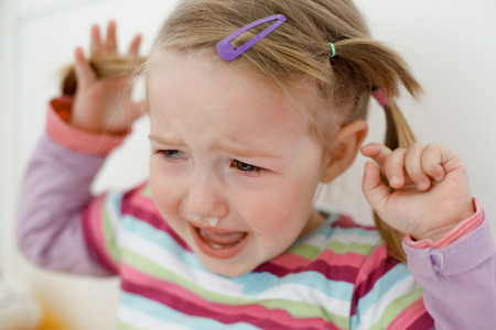 Crying little toddler, having a tantrum during a terrible two phase, raging in her crib. Stock Photo