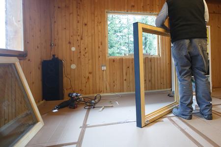 eficiencia: Trabajador que se prepara para instalar nuevas ventanas de tres paneles de madera en una vieja casa de madera. renovación del hogar, vida sostenible, el concepto de eficiencia energética. Foto de archivo