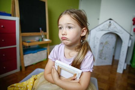 fille triste: Solitaire et triste petite fille assise sur le sol, étant bleu et manque quelqu'un.