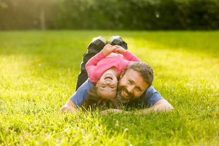 devoted: Devoted father and daughter lying on grass, enjoying each others company, bonding, playing, having fun in nature on a bright, sunny day. Stock Photo