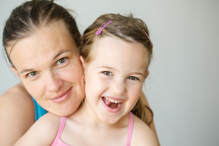 Mother and daughter embracing, smiling, being affectionate, happy and loving.