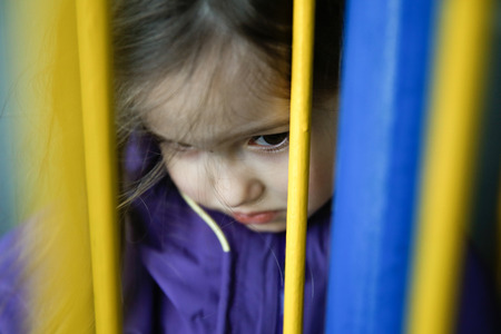 a situation alone: Thoughtful and sad little girl hiding behind fence, feeling blue and distressed.