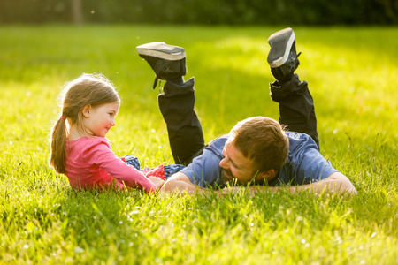 connection connections: Devoted father and daughter enjoying eachothers company, bonding, talking, having fun in nature on a bright, sunny day. Stock Photo