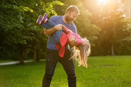 Toegewijde vader spinnen zijn dochter in cirkels, lijmen, spelen, plezier in de natuur op een heldere, zonnige dag.
