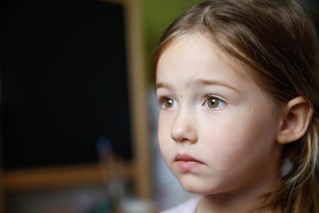 fille triste: Réfléchi et triste petite fille assise sur le sol, étant bleu et manque quelqu'un. Banque d'images