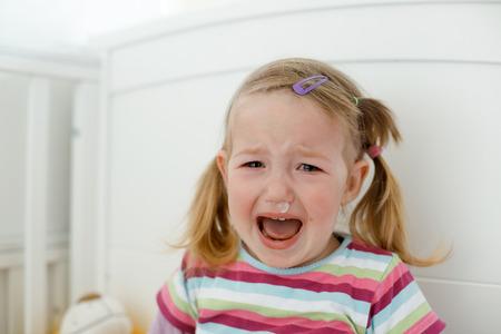Huilende kleine peuter, met een woedeaanval tijdens een verschrikkelijke twee fasen, woedt in haar wieg. Stockfoto