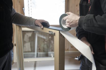 eficiencia: Los trabajadores que aplican una cinta aislante autoadhesiva RAL para instalar nuevas ventanas, tres paneles de madera en una casa de madera. renovación del hogar, vida sostenible, el concepto de eficiencia energética. Foto de archivo