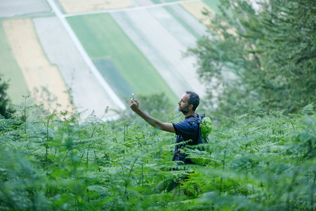 disoriented: Hiker looking for his GPS signal on a smartphone, disoriented in lush woodlands, trying to find a way out.
