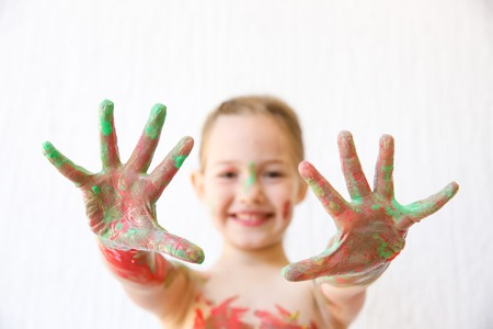 finger paint: Little girl showing her hands, covered in finger paint after painting a picture and her body with it. Stock Photo