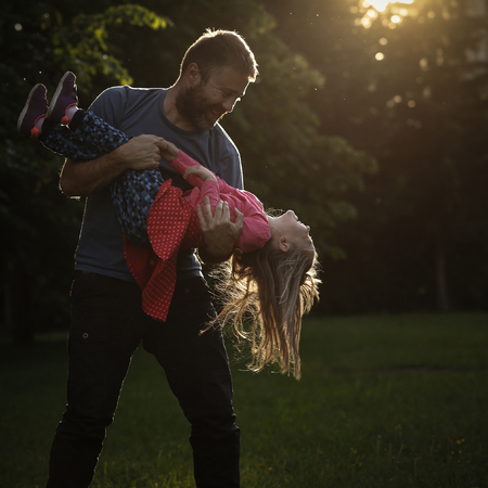 devoted: Devoted father spinning his daughter in circles, bonding, playing, having fun in nature on a bright, sunny day. Stock Photo