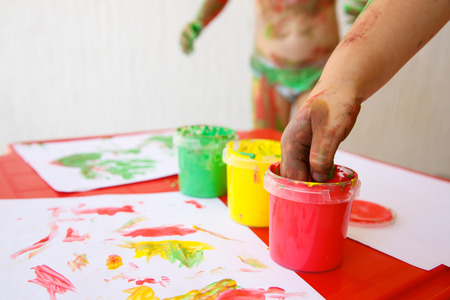 washable: Child dipping fingers in washable, non-toxic finger paints, painting a drawing.