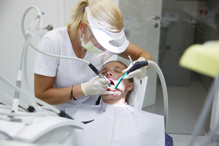 Woman at dental office, dentist examining and cleaning her teeth of tartar and plaque, preventing periodontal disease. Dental hygiene, painful procedures and prevention concept.