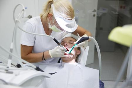 Vrouw bij tandartspraktijk, tandarts onderzoeken en haar tanden schoonmaakt van tandsteen en plaque, het voorkomen van parodontitis. Tandverzorging, pijnlijke procedures en preventie concept. Stockfoto