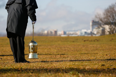 cremated: Funeral director, undertaker, starting to scatter ashes of a cremated human on a designated field for ash scattering.