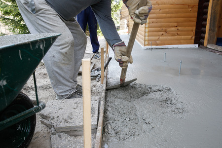 improvisation: Masons filling wood form with a shovel of concrete mix for floor base in front of the house.