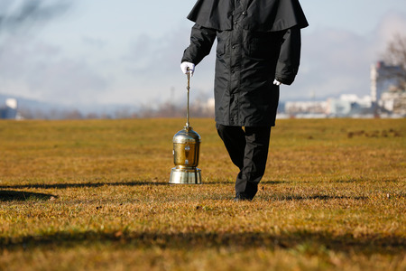 cremated: Funeral director, undertaker, carrying an extravagant urn with ashes of a cremated human during a formal scattering ceremony.
