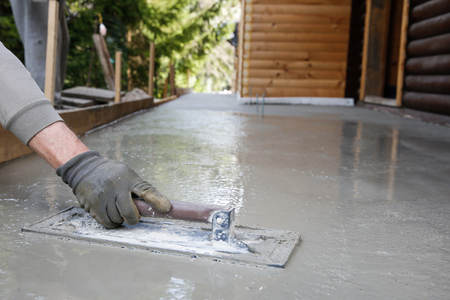concrete form: Mason leveling and screeding concrete floor base with square trowel in front of the house.