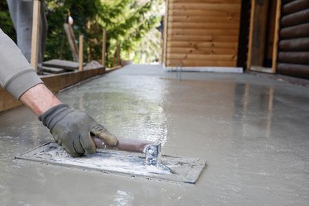 suelos: Mason nivelación y screeding base de suelo de cemento con una llana plaza en frente de la casa. Foto de archivo