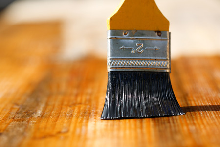 home exterior: Paintbrush sliding over wooden surface, protecting wood for exterior influences, weathering, insects and fungus. Carpentry, woodwork, home improvement, do-it-yourself concept and background.