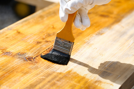 weathering: Carpenter holding a paintbrush over wooden surface, protecting wood for exterior influences and weathering. Carpentry, wood treatment, hard at work, home improvement, do-it-yourself concept. Stock Photo