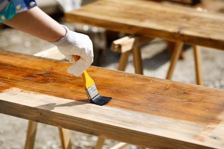 sawhorse: Painting wood with wood protection paint for weathering, fungus and insects on sawhorses. Outdoor protection, carpentry, hard at work, home improvement, do-it-yourself concept. Stock Photo