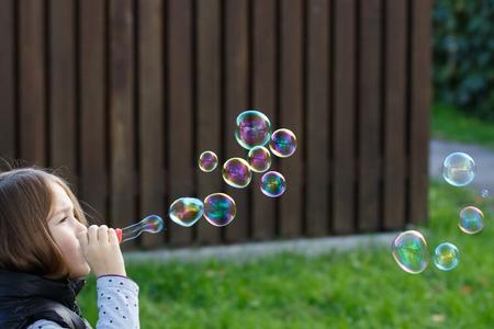 infancia: Pequeñas burbujas soplan de la chica, divertirse, disfrutar de la infancia sin preocupaciones. Juventud, diversión y juegos para niños concepto con el espacio de la copia. Foto de archivo