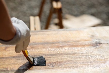 doityourself: Gloved hand holding a paintbrush over wooden surface, protecting wood for exterior influences and weathering. Carpentry, wood treatment, hard at work, home improvement, do-it-yourself concept.