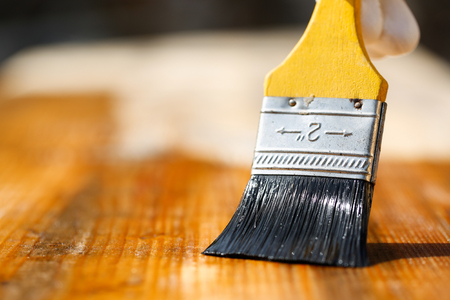 doityourself: Paintbrush sliding over wooden surface, protecting wood for exterior influences, weathering, insects and fungus. Carpentry, woodwork, home improvement, do-it-yourself concept and background.
